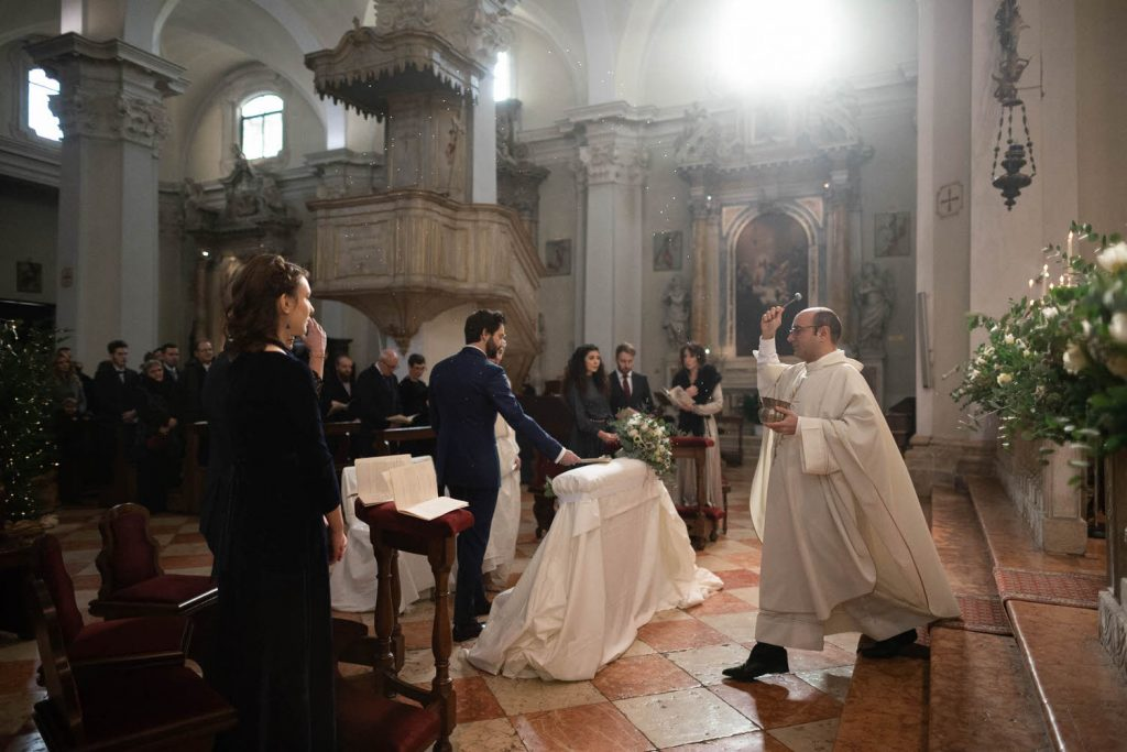 A dynamic ceremony photo showing a priest in motion as he moves toward the bride and groom blessing them with holy water, his skirts following behind him and natural light flooding through the windows of the church, by luxury wedding photographer Francesco Bognin