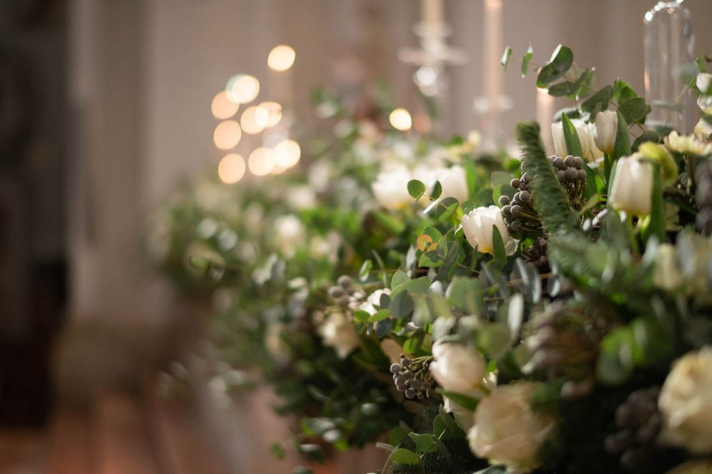 A closeup of a unique winter bridal bouquet with twinkling lights in the background, by luxury wedding photographer Francesco Bognin