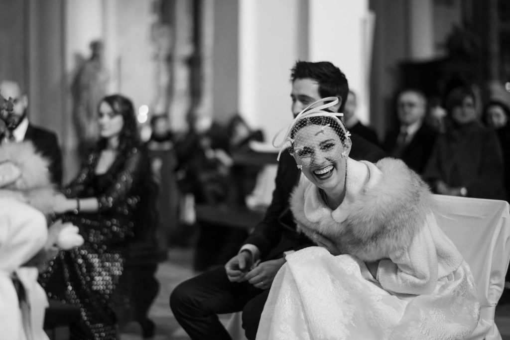 A black and white photo during a ceremony with bride and groom seated and the bride dressed bent over in laughter and wearing a wide smile, by luxury wedding photographer Francesco Bognin