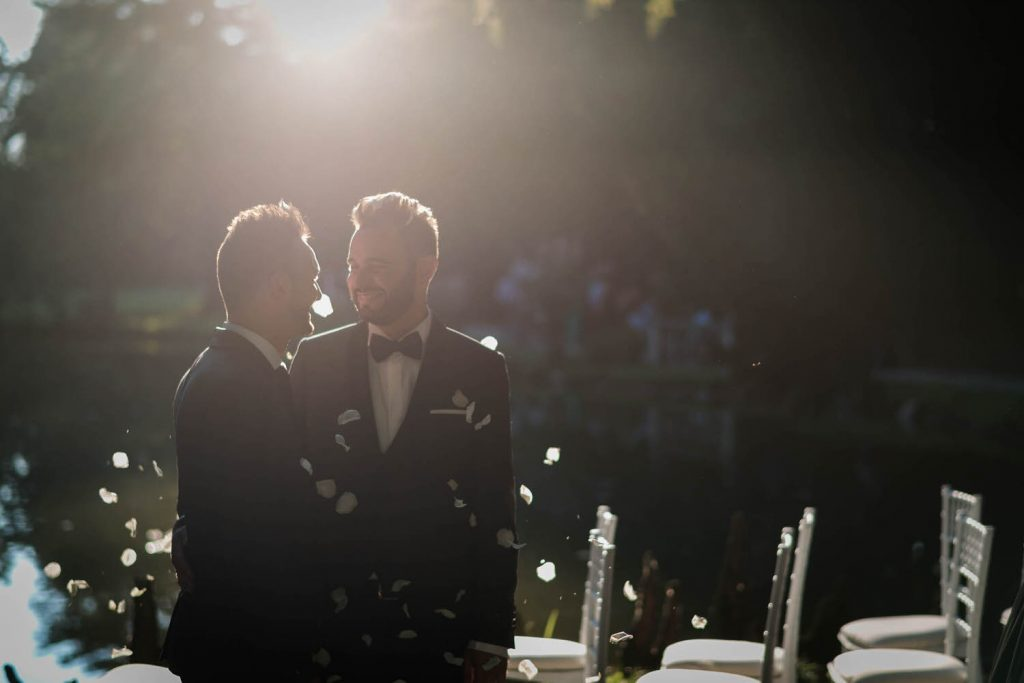 Two grooms in tuxedos looking into each others eyes with the sun behind them and flower petals falling around them after their ceremony in Italy, shot by luxury wedding photographer Francesco Bognin