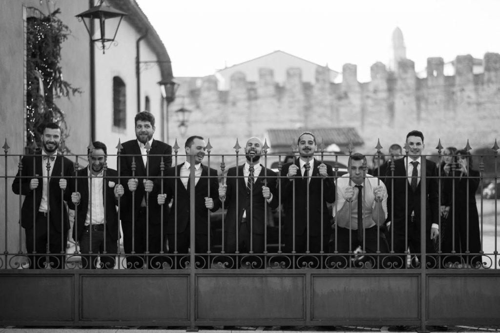 A group of men stand expectantly and with animated faces and postures behind a fence and with a castle wall in the distance behind them, in black and white by luxury wedding photographer Francesco Bognin
