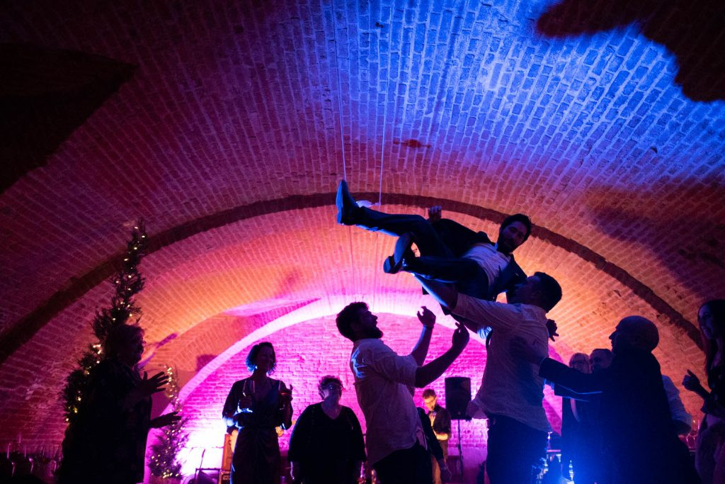 A groom is suspended in air after being tossed upward by his groomsman. Multiple people stand in partial or full silhouette in a domed and ancient Italian space lit vibrantly in orange blue and pink, bu luxury wedding photographer Francesco Boginin