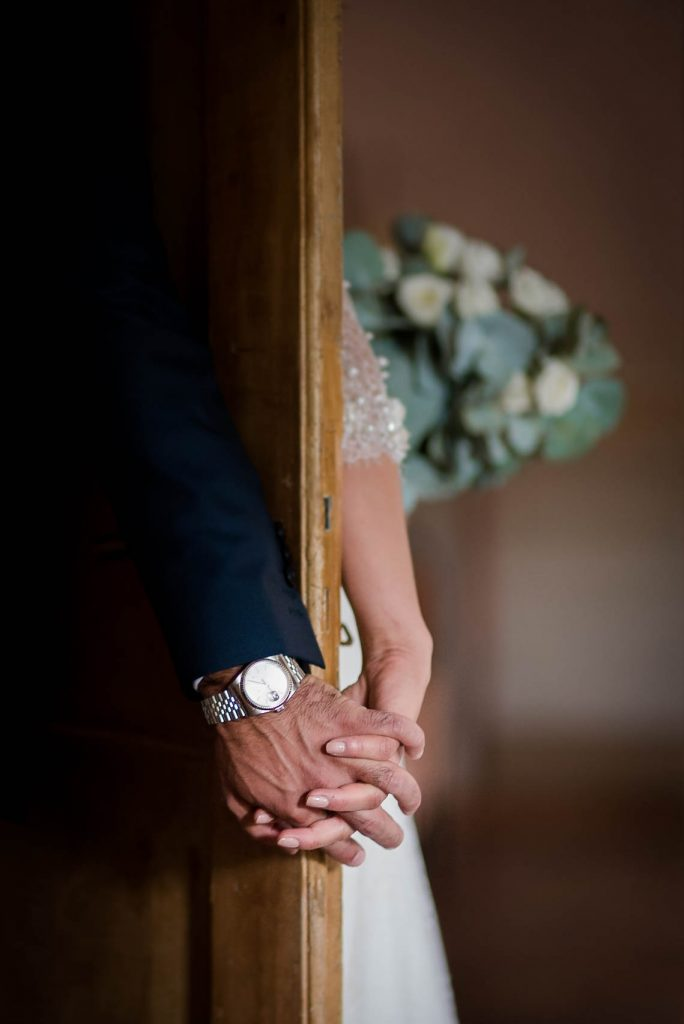 The hands of a bride and groom meet and intertwine from opposite sides of a door before their first look. His watch and her bouquet are visible, by luxury wedding photographer Francesco Bognin