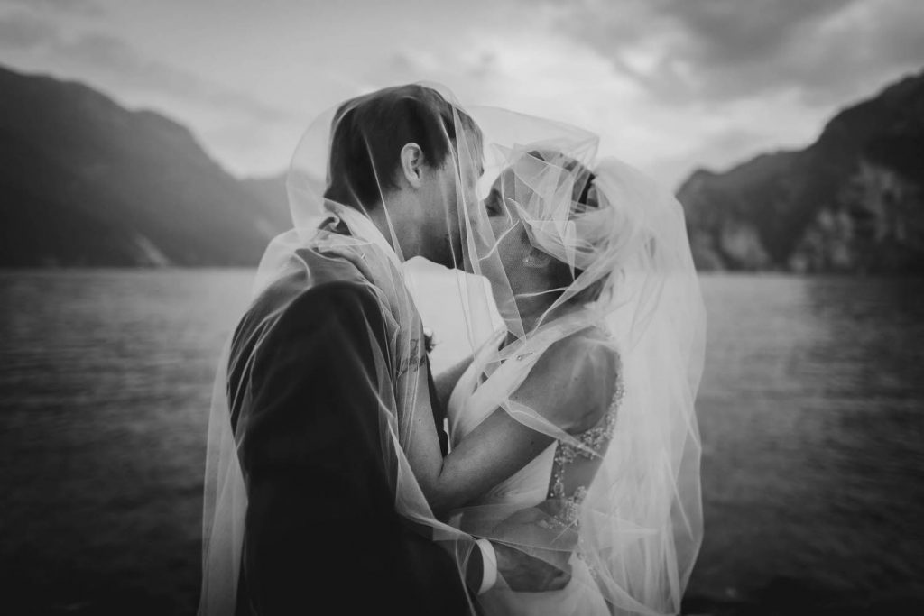 A black and white profile portrait of a bride and groom in an embrace and sharing a kiss under her veil with the hills and waters of Lake Como in the distance, by luxury wedding photographer Francesco Bognin
