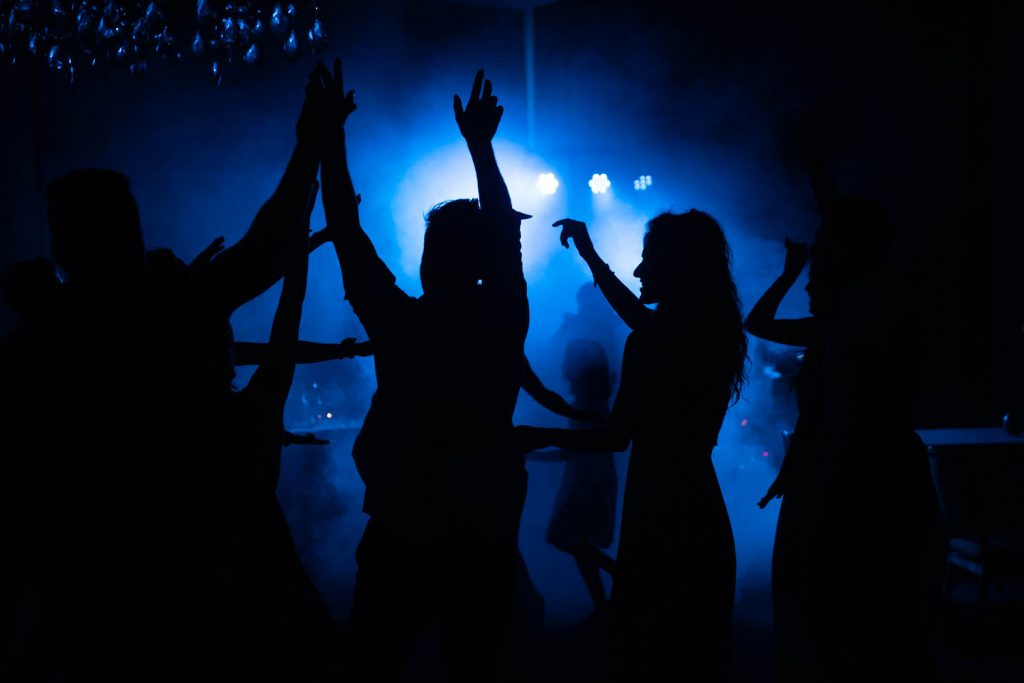 Multiple people dancing in silhouette with blue light shining behind them by luxury wedding photographer Francesco Bognin