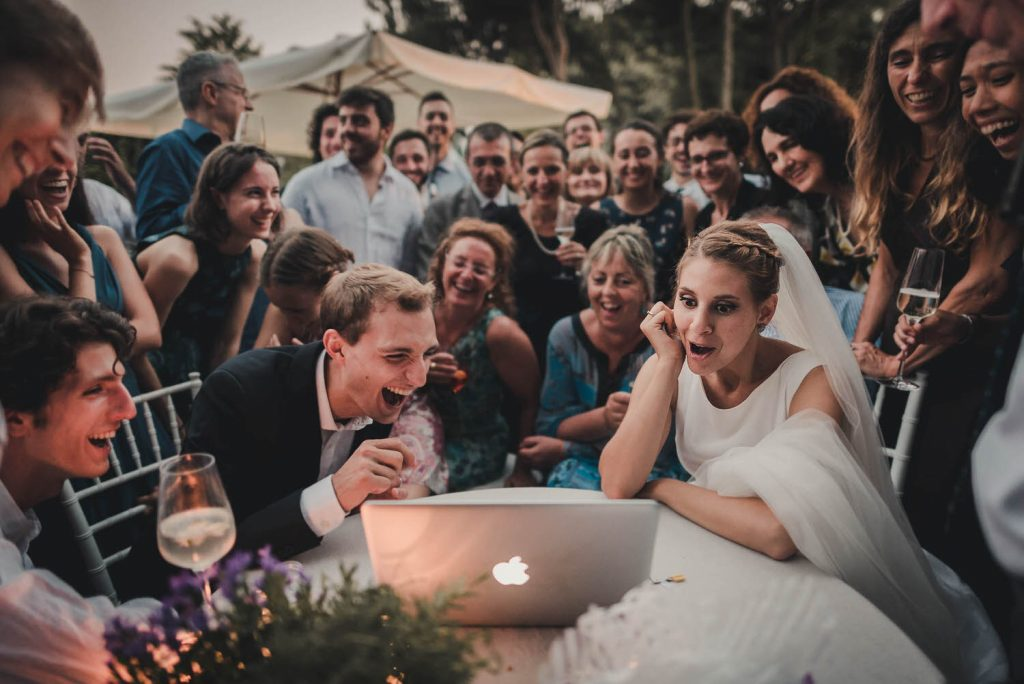 A large group of people stand and sit behind a bride and groom who sit at a table with an apple computer in front of them, all of them wearing animated expressions as they preview their wedding photos from that day, by luxury wedding photographer Francesco Bognin