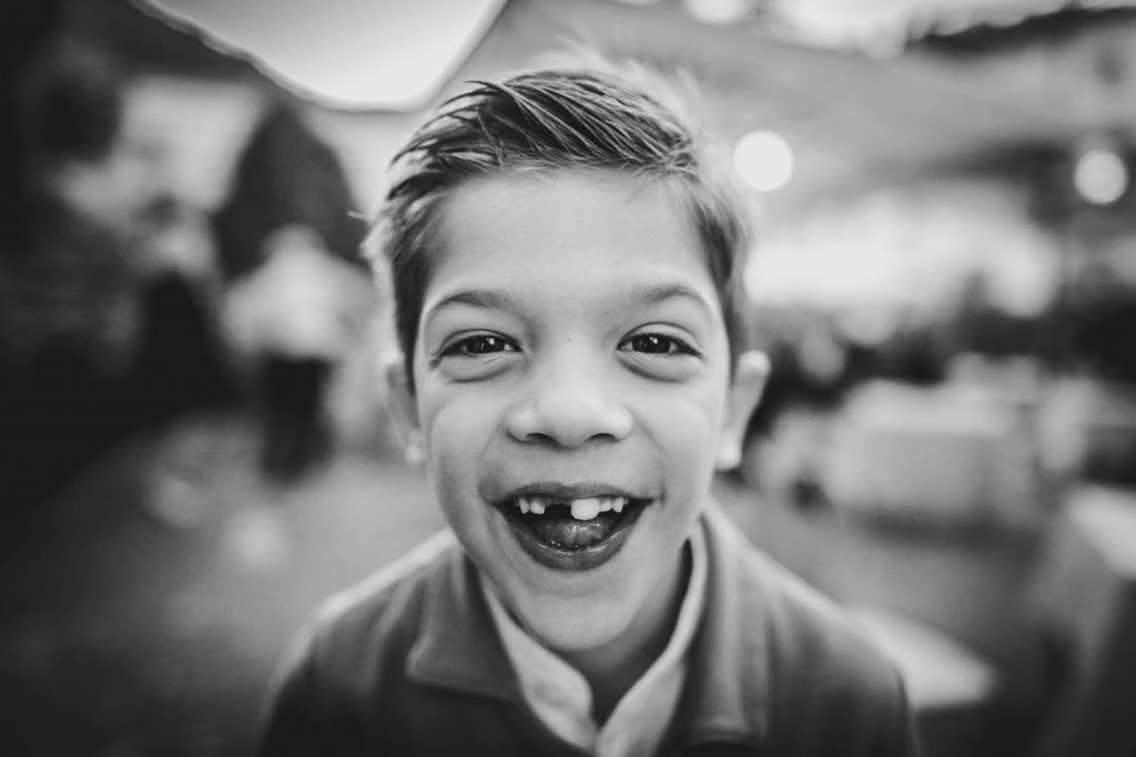 A black and white photo of a child smiling wildly with missing teeth, by luxury wedding photographer Francesco Bognin