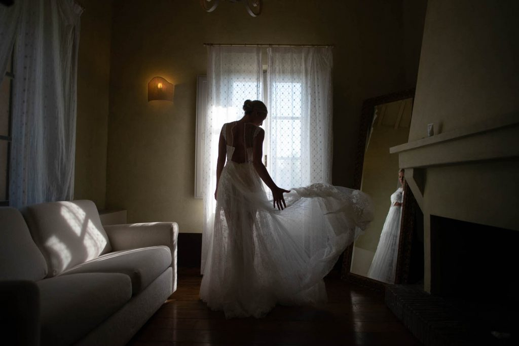 A bride stands in a dimly lit room tossing the skirt of her dress to the side as she faces a glowing window, by luxury wedding photographer Francesco Bognin