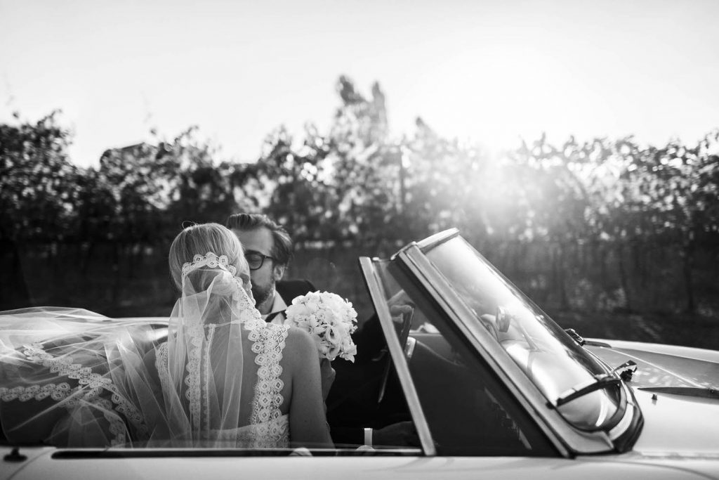As seen from the behind the bride, a bride and groom share a kiss in a convertible car, she wearing her veil and holding a bouquet with the sunset glowing through the trees behind, featured in Vogue Sposa by luxury wedding photographer Francesco Bognin