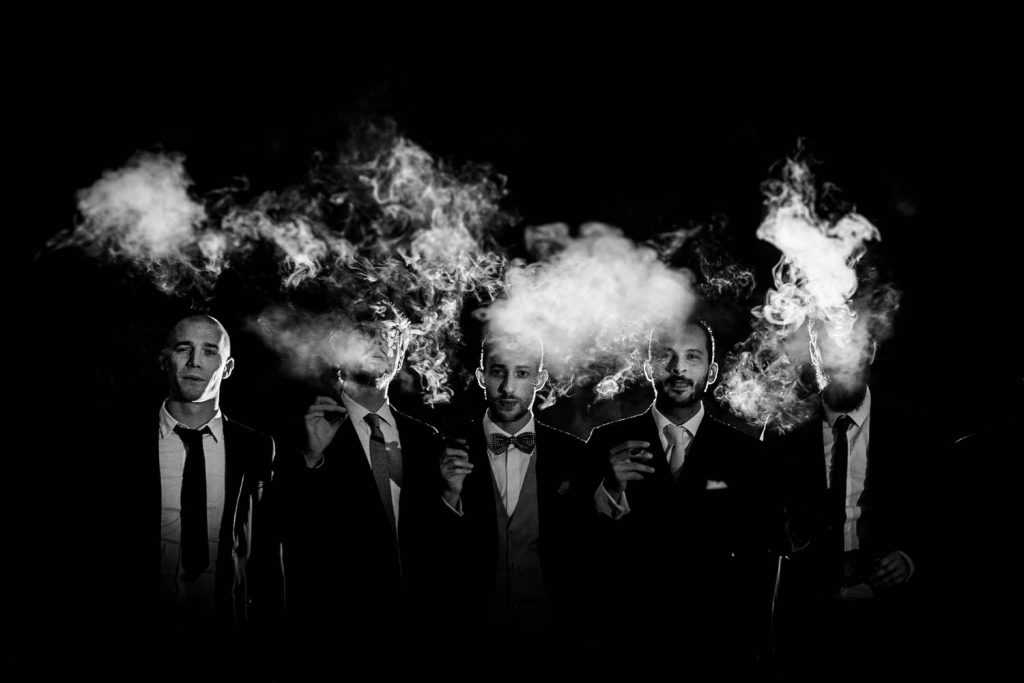 Fine art black and white portrait of groom and groomsmen standing in a line in tuxedos and suits, all smoking against an all black background and clouds of smoke dancing above an around them, by luxury wedding photographer Francesco Bognin