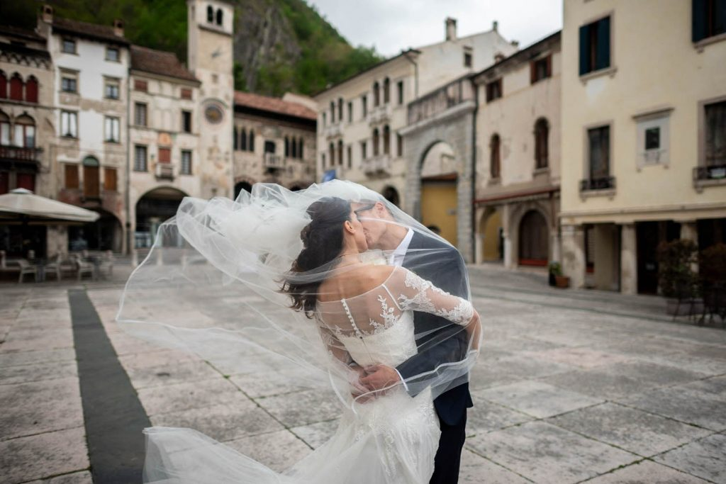 A bride and groom sway in an embrace and share a kiss while under her veil which flies away in the wind, set in a typical italian piazza, by luxury wedding photographer Francesco Bognin