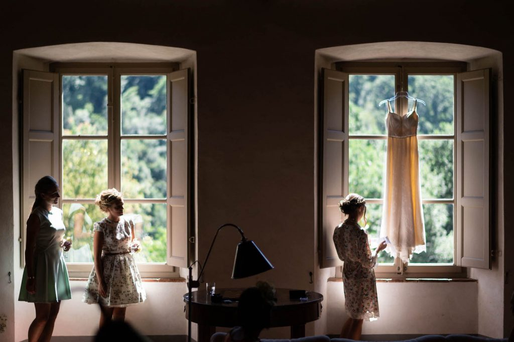 A symmetrical setting in a dim room lit by natural light flooding through two identical windows with a wedding dress hanging in one window and three people standing in front of the windows, their edges lit by natural light in a villa room in Italy, by luxury wedding photographer Francesco Bognin