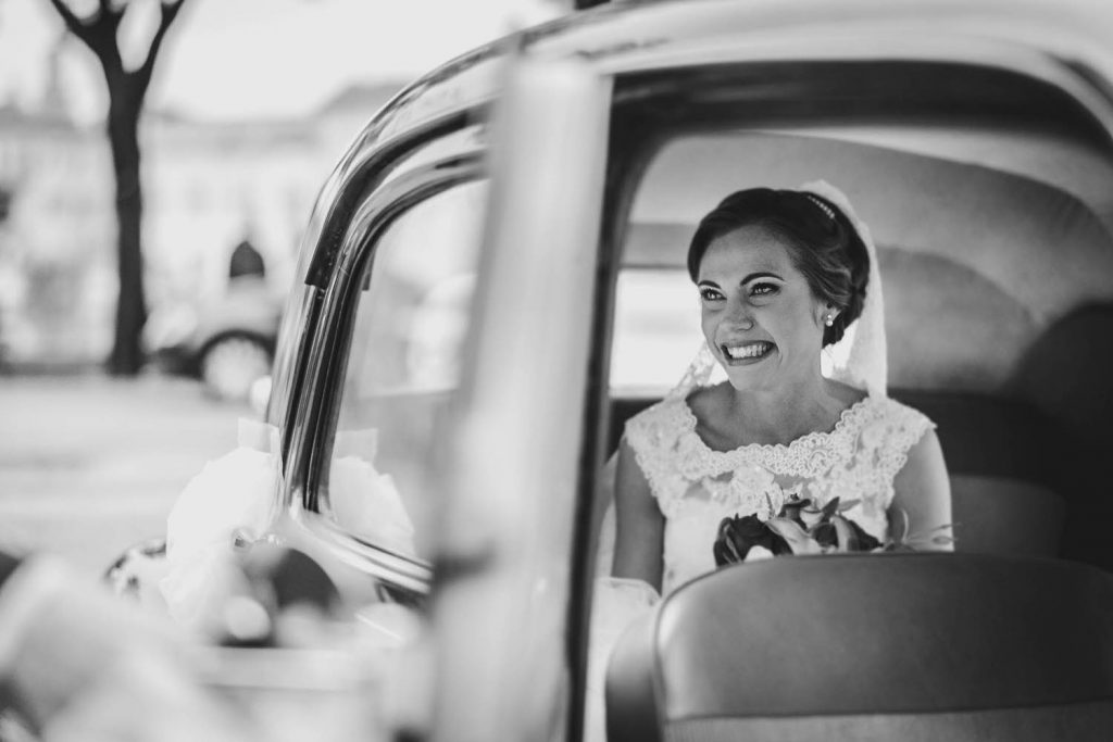 A smiling and beaming bride looks out of the window of the car she has just arrived in, by luxury wedding photographer Francesco Bognin