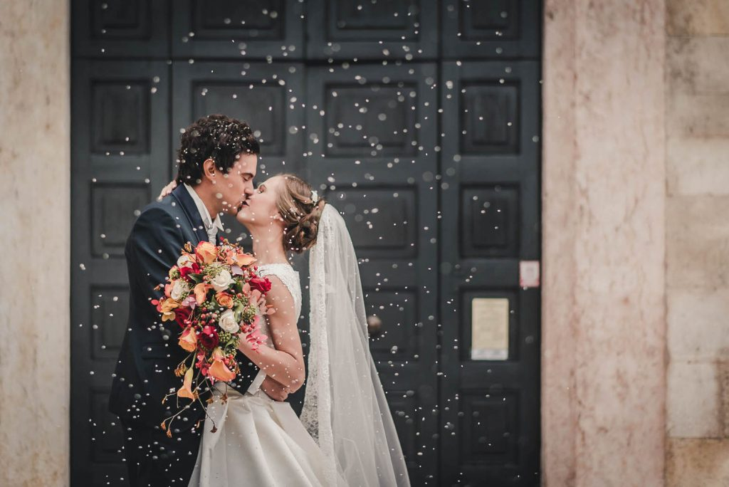 A post-ceremony profile portrait of a bride and groom in embrace and sharing a kiss, with her colourful bouquet in one hand and her veil trailing behind her as rice falls from the sky like crystals, by luxury wedding photographer Francesco Bognin