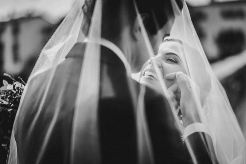 A bride turns her smiling face up to her groom and he caresses her face, both of them beneath her veil and seen from behind him and over his shoulder, by luxury wedding photographer Francesco Bognin