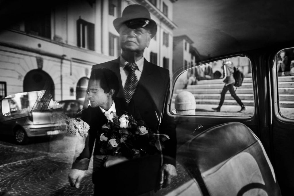 Fine art black and white photo showing a bride and groom kissing in a car as well as the reflection of an older man in a suit on the window of the car and a pedestrian visible walking down the street by luxury wedding photographer Francesco Bognin