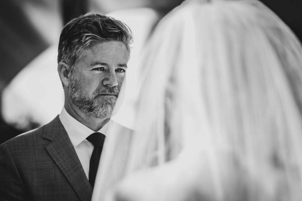 Black and white portrait of a misty eyed groom looking at his bride who we see veiled from behind, in Pasadena California USA by luxury wedding photographer Francesco Bognin