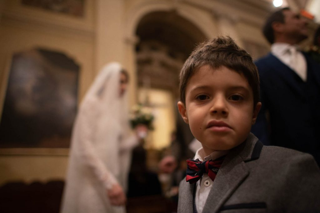 A close up portrait of a child looking into the camera with a crooked half smile and attitude with the veiled bride visible walking in the background by luxury wedding photographer Francesco Bognin