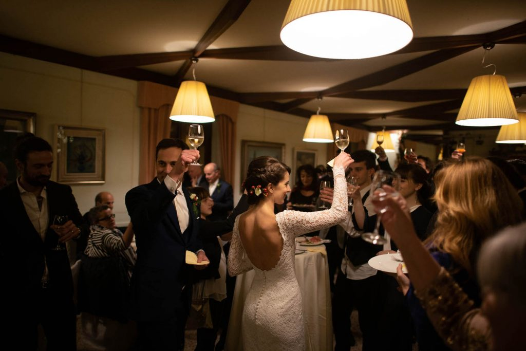 A bride wearing a slim gown with a low back raises her glass in a toast and is surrounded by other people in suits and tuxedos set in a restaurant by luxury wedding photographer Francesco Bognin