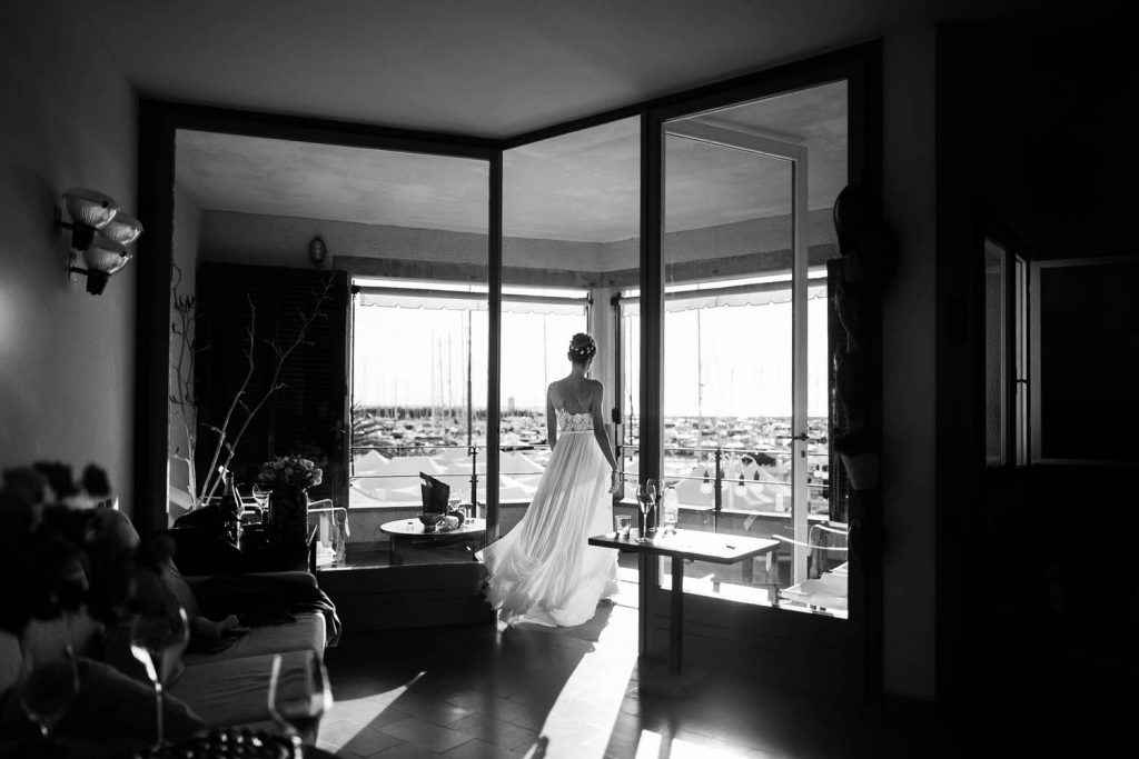 A bride in her gown floats through an architectural room toward large windows in black and white by luxury wedding photographer Francesco Bognin