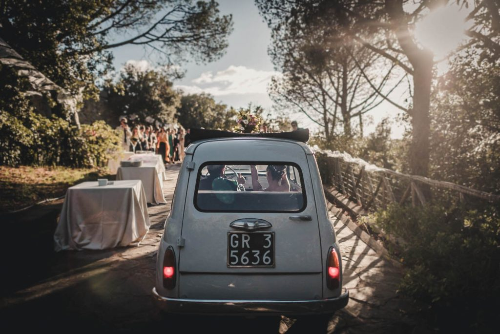A bride in groom in a Fiat car driving away down a small tree lined road by luxury wedding photographer Francesco Bognin