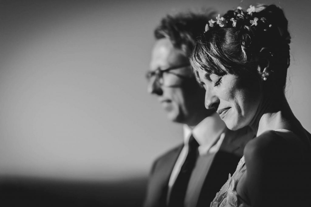 A fine art black and white close up portfolio portrait of a bride and groom wearing expressions of joy by luxury wedding photographer Francesco Bognin