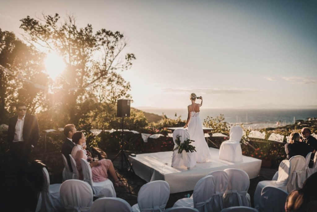 A bride stands on a raised platform  with her back to guests, her arm raised to take a selfie with the sun set and hills in the distance by luxury wedding photographer Francesco Bognin