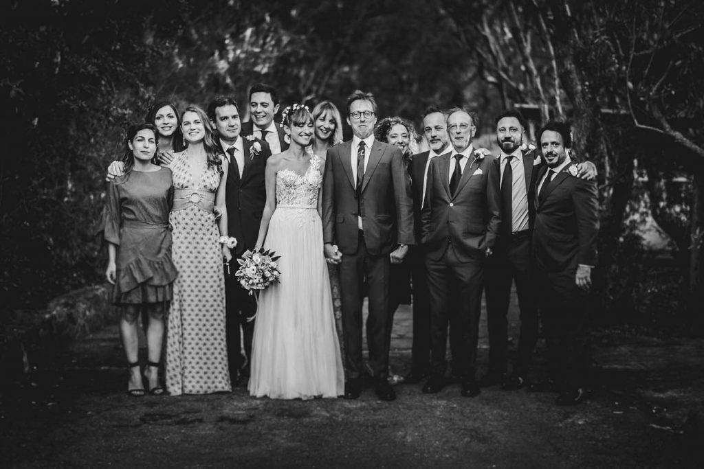 A smiling bride poses with her groom who wears a silly expression and they are surrounded by family and friends in a black and white fine art photo by luxury wedding photographer Francesco Bognin
