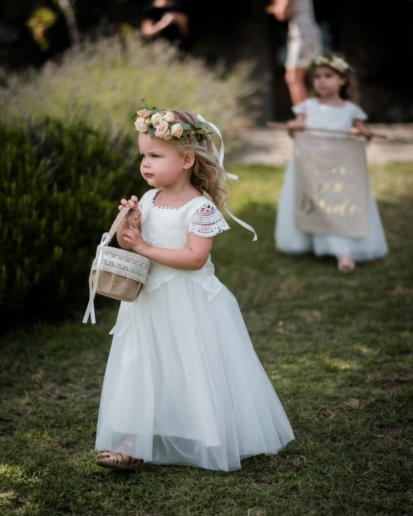 A blonde toddler wears a flower girl gown and flower crown and reaches her hand into her basket of flowers as another flower girl walks behind in the distance by luxury wedding photographer Francesco Bognin