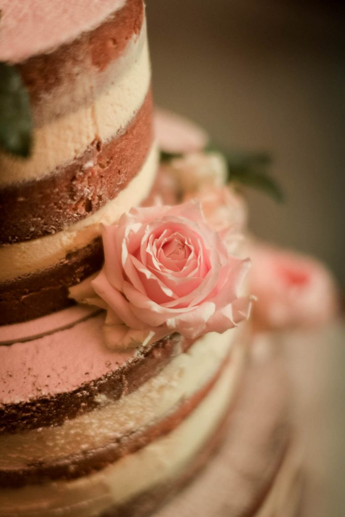 A close up portrait of a naked wedding cake decorated with pink roses by luxury wedding photographer Francesco Bognin