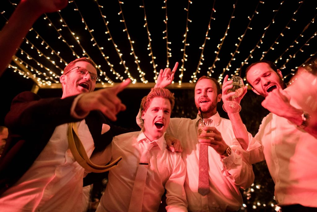 A group of men celebrate and huddle around a wide angle shot lit by orange and pink with lights creating lines of light above by luxury wedding photographer Francesco Bognin