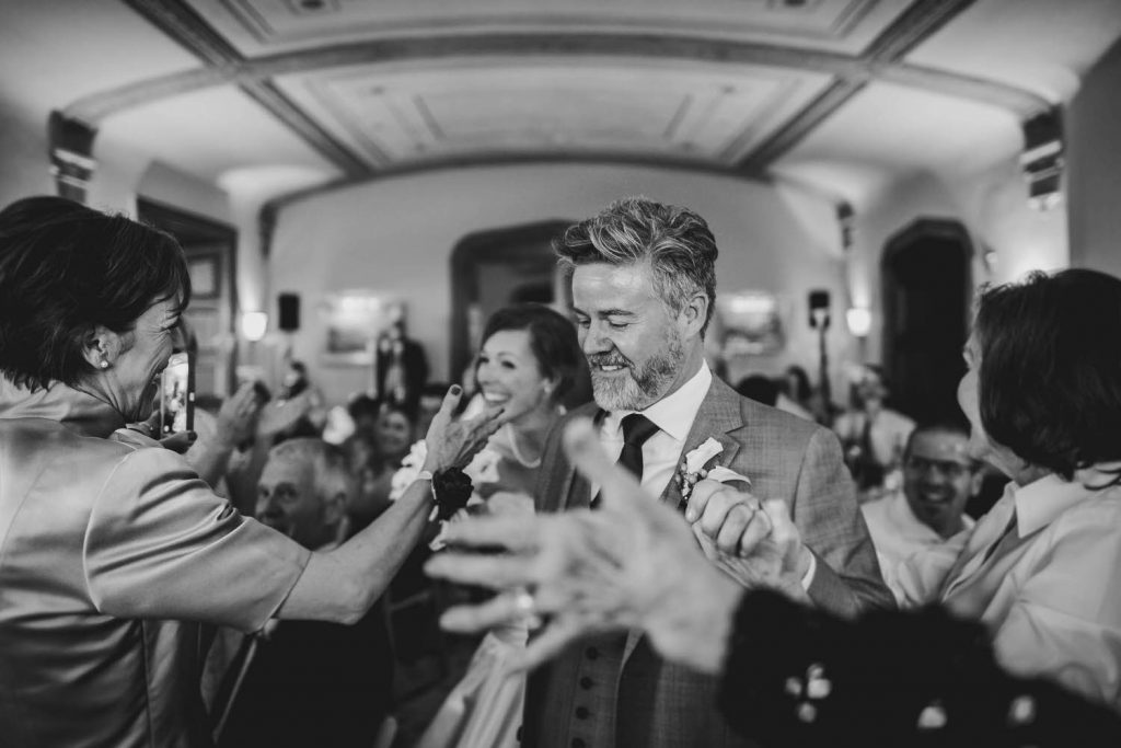 Black and white reportage photo of a bride and groom leaving their ceremony and surrounded by the arms and hands of loved ones as they smile in Pasadena California USA by luxury wedding photographer Francesco Bognin