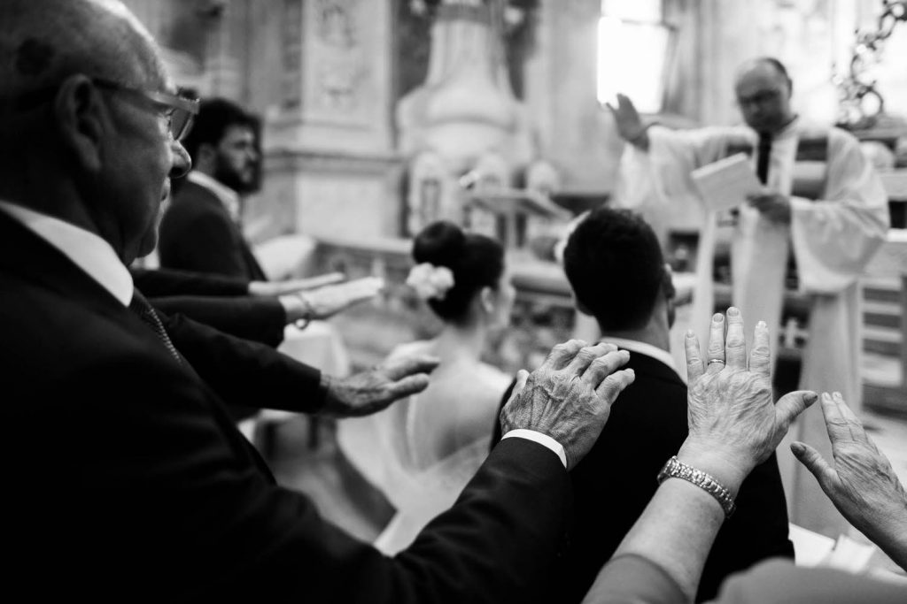 Guests surround a bride and groom with their hands extended in prayer during a ceremony in a church by luxury wedding photographer Francesco Bognin