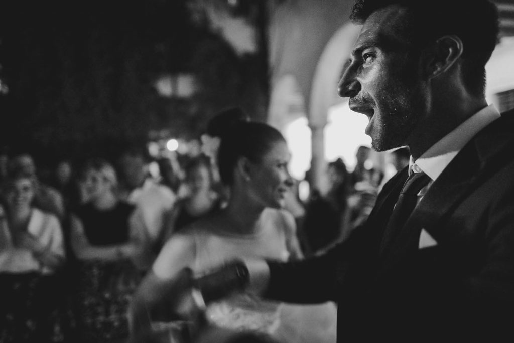 A groom wears a vivid and celebratory expression in a profile portrait with his mouth opened widely and his arm raised and his bride right behind him and guests behind her by best in italy luxury wedding photographer Francesco Bognin