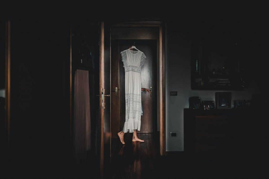 Fine art reportage photo of wedding gown passing through a hall as seen through a doorway with only the feet of the carrier visible just below the dress by best in Italy luxury wedding photographer Francesco Bognin