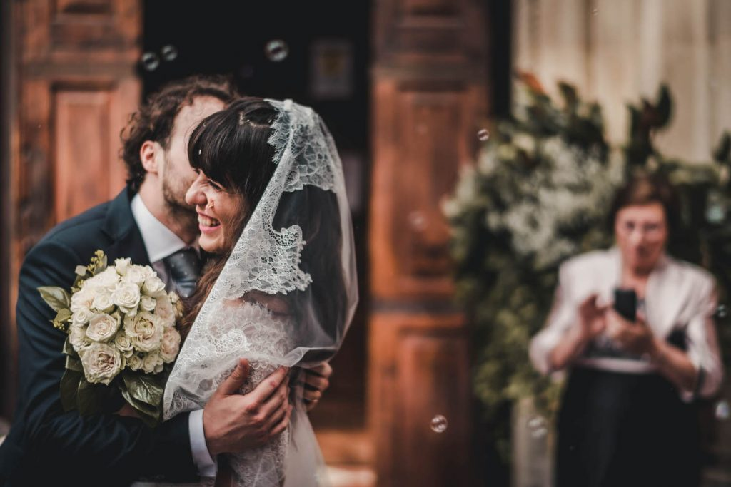 A groom embraces his bride and holds her close as he kisses her cheek enthusiastically she wearing veil and holding a bouquet with a woman visible in the background by best in Italy luxury wedding photographer Francesco Bognin