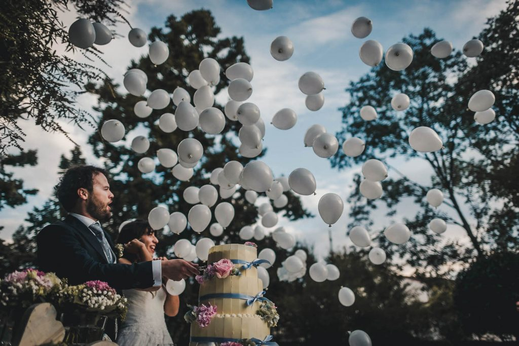 A bride and groom stand in front of their wedding cake and look up to the sky with amazement as hundreds of white balloons fly above by best in Italy luxury wedding photographer Francesco Bognin