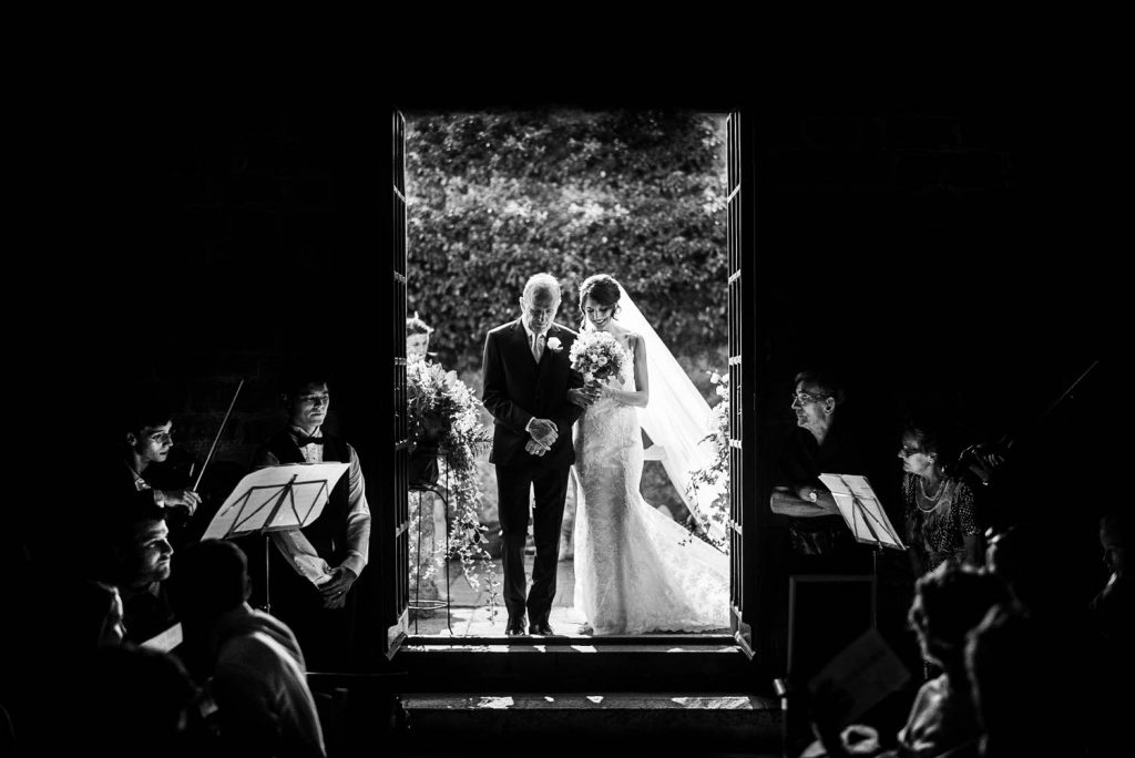 A bride and her father brightly lit by the sun enter a dim church with orchestra flanking the aisle by best in Italy luxury wedding photographer Francesco Bognin
