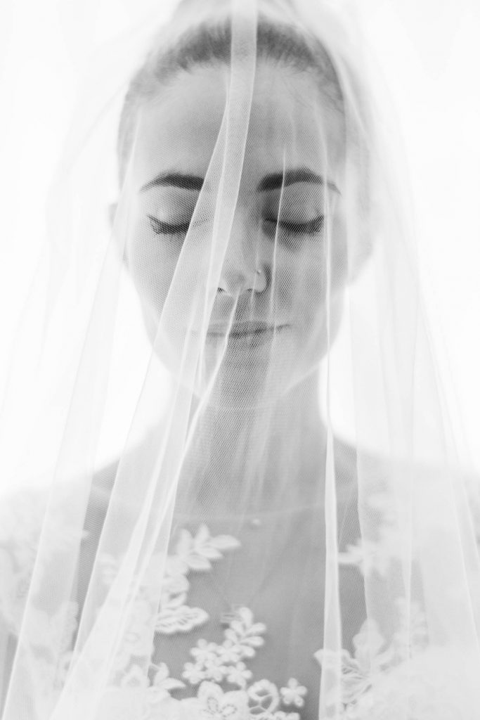 A stunning close up portrait of a bride under her veil with eyes closed in black and white against a glowing white background in Italy by luxury wedding photographer Francesco Bognin