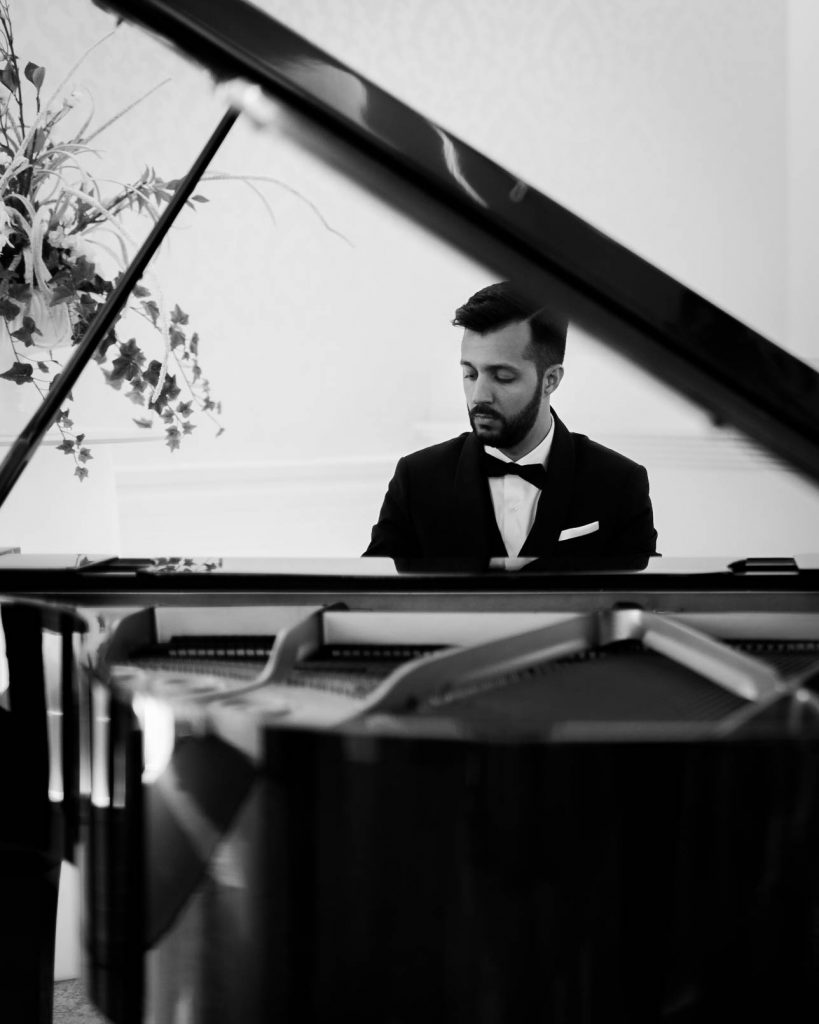 A groom in a tuxedo plays a grand piano as seen from the far end of and through the piano by luxury wedding photographer best in Italy Francesco Bognin