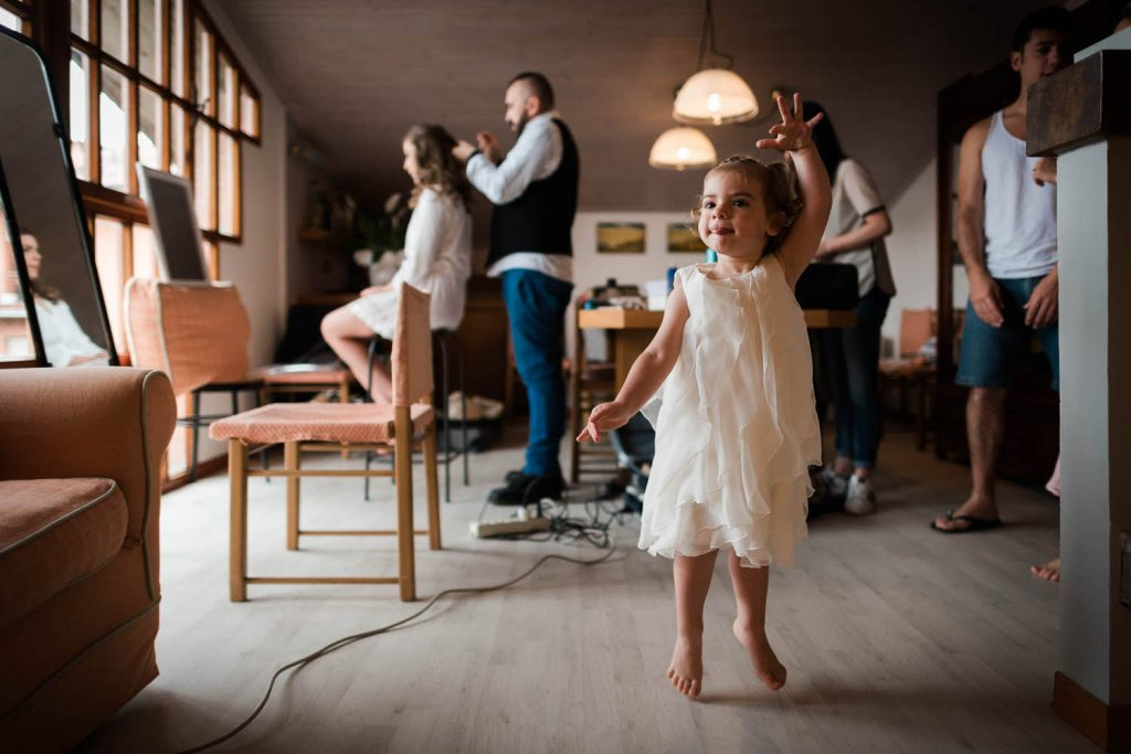 A small child dances and floats on her toes millimetres over the floor and adults are getting ready in the background by best in Italy luxury wedding photographer Francesco Bognin