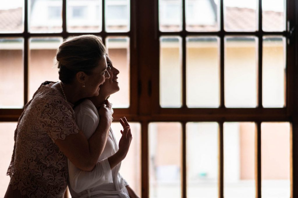 A mother embraces a daughter from behind in a profile portrait set against the natural light from a graphic window in the background by best in Italy luxury wedding photographer Francesco Bognin