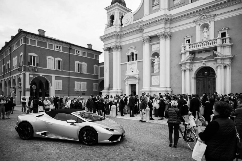 A Lamborghini is parked in front of a large Italian church and guests form a circle around it in black and white luxury fine art style by best in Italy wedding photographer Francesco Bognin