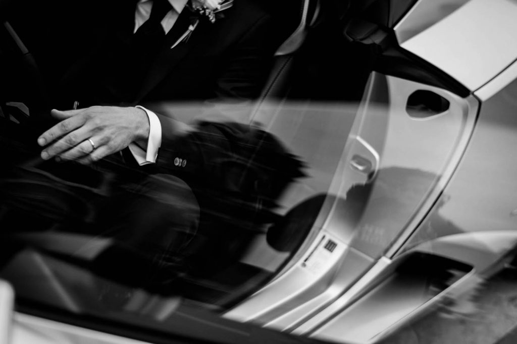 The torso and hand of a groom in a suit is visible from above as he exits a Lamborghini with reflections casting additional reflections by luxury wedding photographer Francesco Bognin