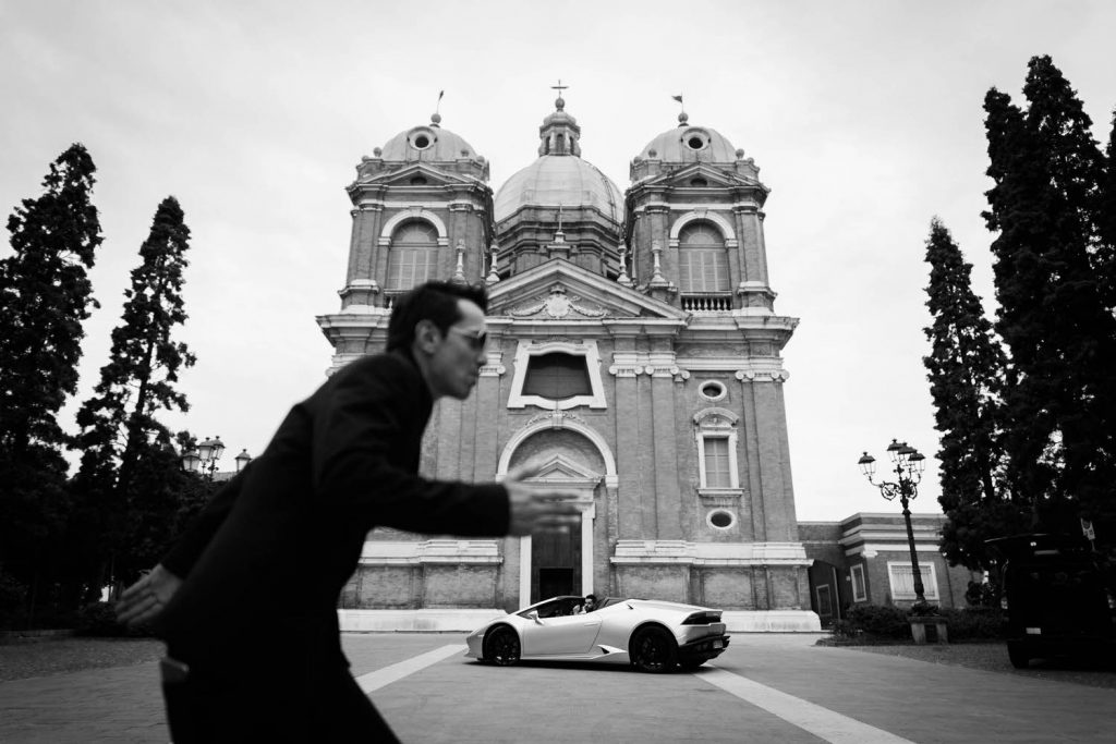 A Lamborghini is parked in front of a large Italian church and a man enters the frame in the foreground running in from the left by fine art luxury wedding photographer Francesco Bognin