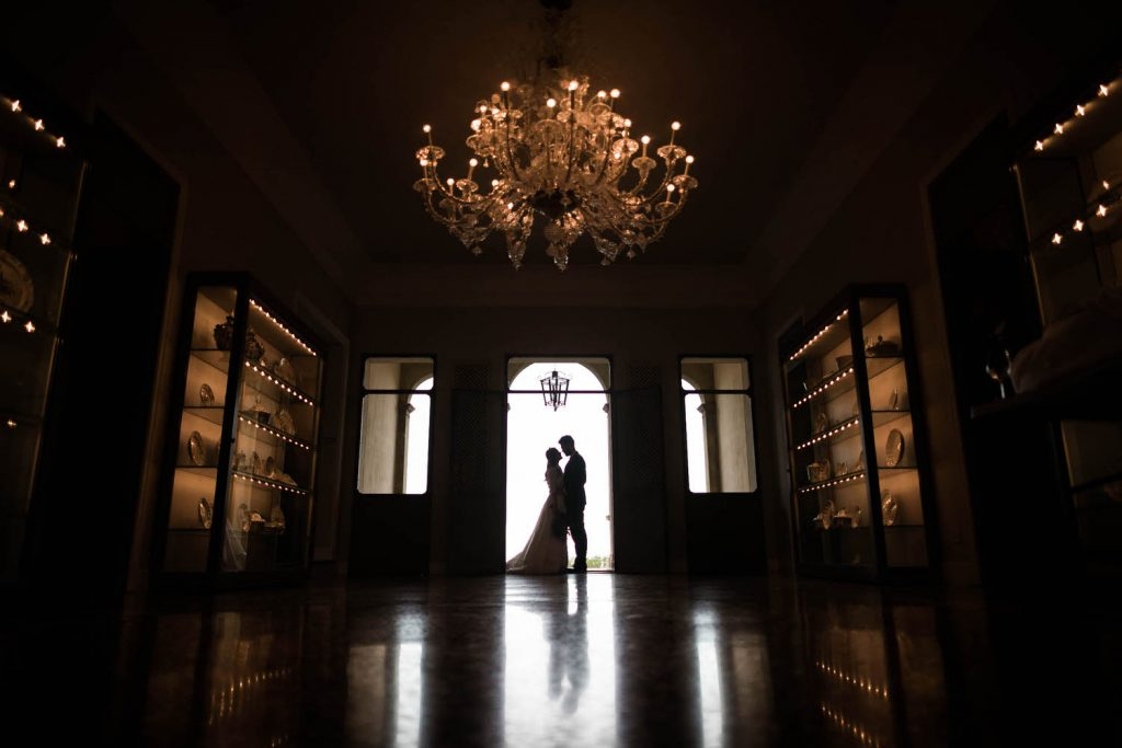 A bride in groom stand in a rounded doorway lit by natural light and embracing in a silhouette in an other wise dim and warmly lit room with a chandelier by best in Italy luxury wedding photographer Francesco Bognin