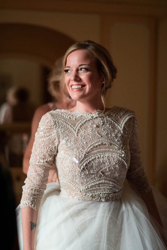 Portrait of a smiling bride looking to the side in her gorgeous beaded and tulle wedding dress in Villa Pizzo Lake Como shot by luxury wedding photographer Francesco Bognin