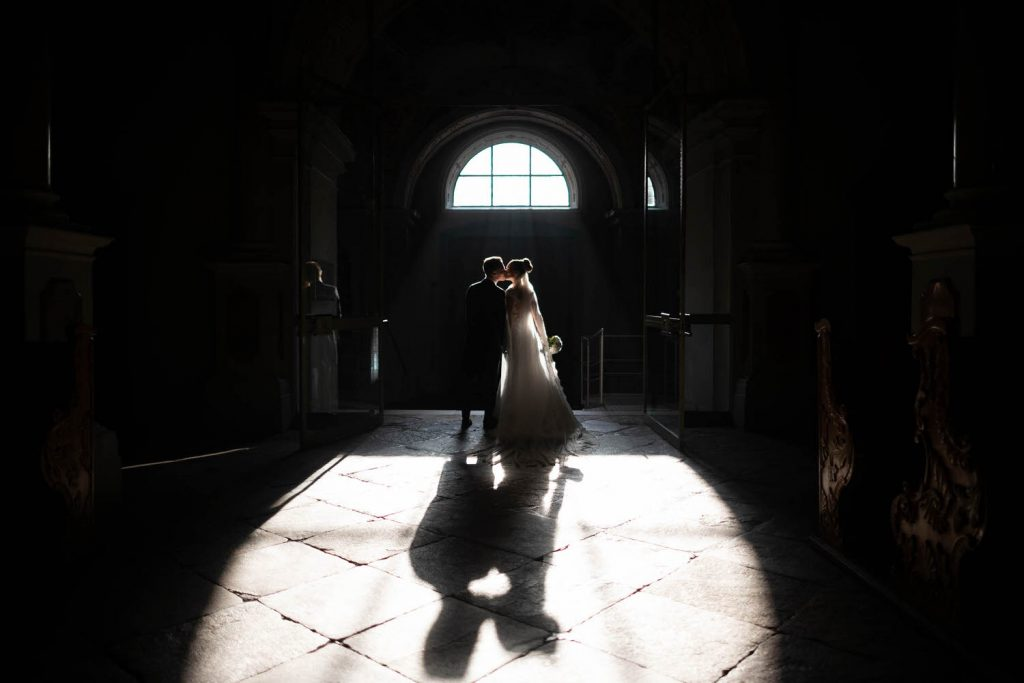 Fairy tale moment as a bride and groom share a kiss as they bathe in light flowing into an otherwise dark church making them seem to glow and casting a perfect shadow on the stone tiles below, in Italy by luxury wedding photographer Francesco Bognin