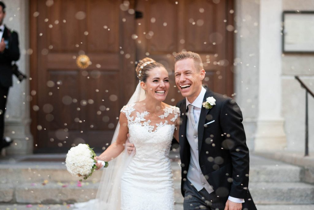 A blonde bride and groom are all smiles as they leave their ceremony and are showered in rice and flower petals in Italy by luxury wedding photographer Francesco Bognin