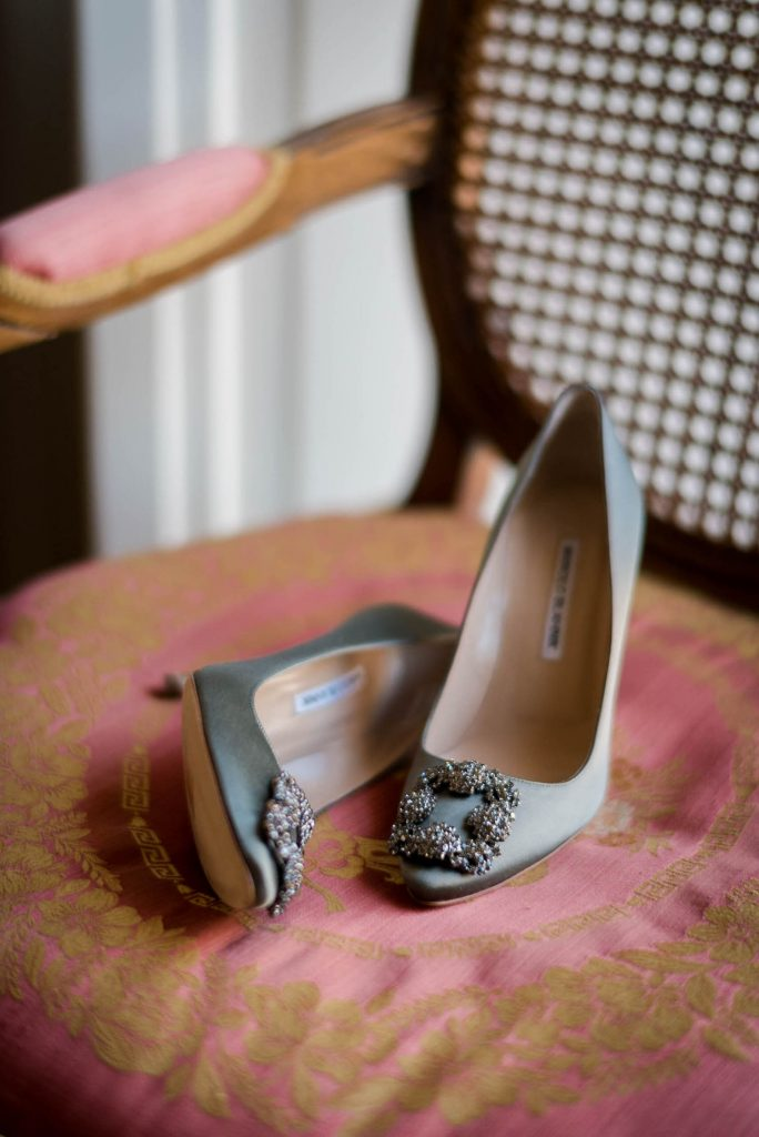 A pair of blue satin Manolo Blahnik pumps with embellished toes sit gracefully on a gold and read upholstered chair in Italy by luxury wedding photographer Francesco Bognin